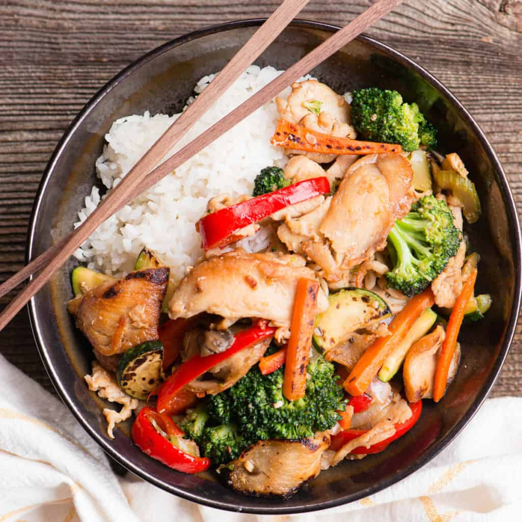 chicken and vegetable stir fry in bowl with rice