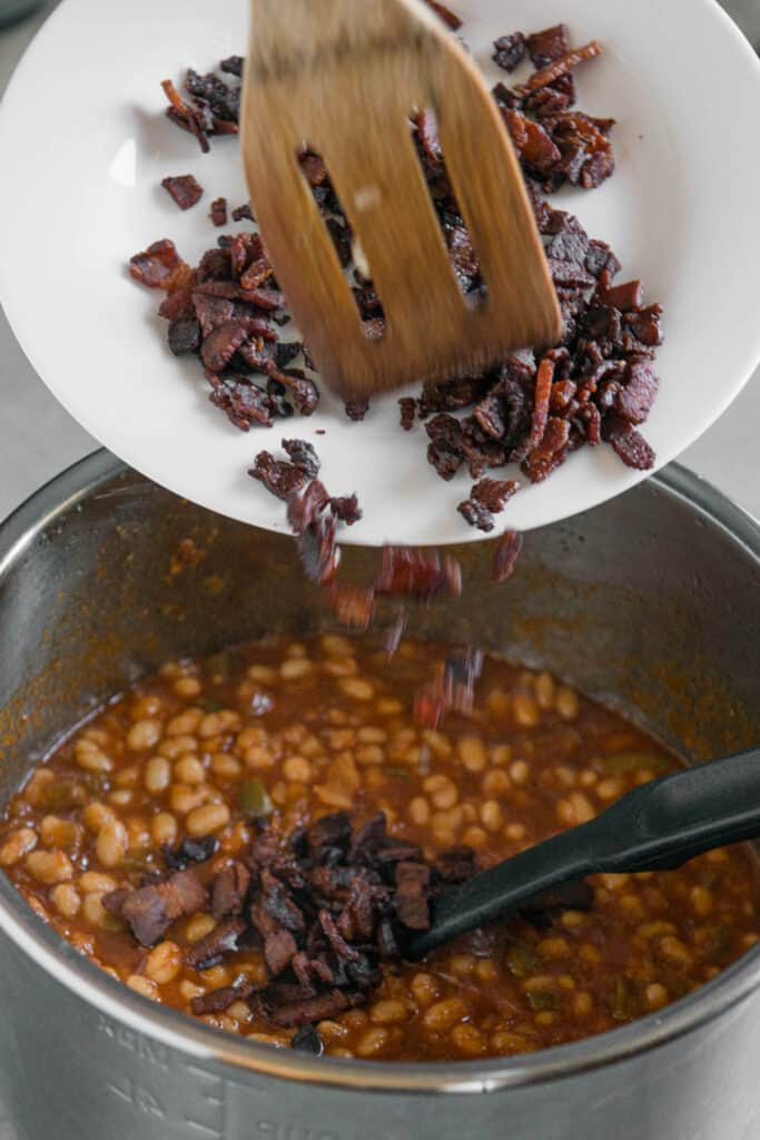 adding cooked crisp bacon to baked beans