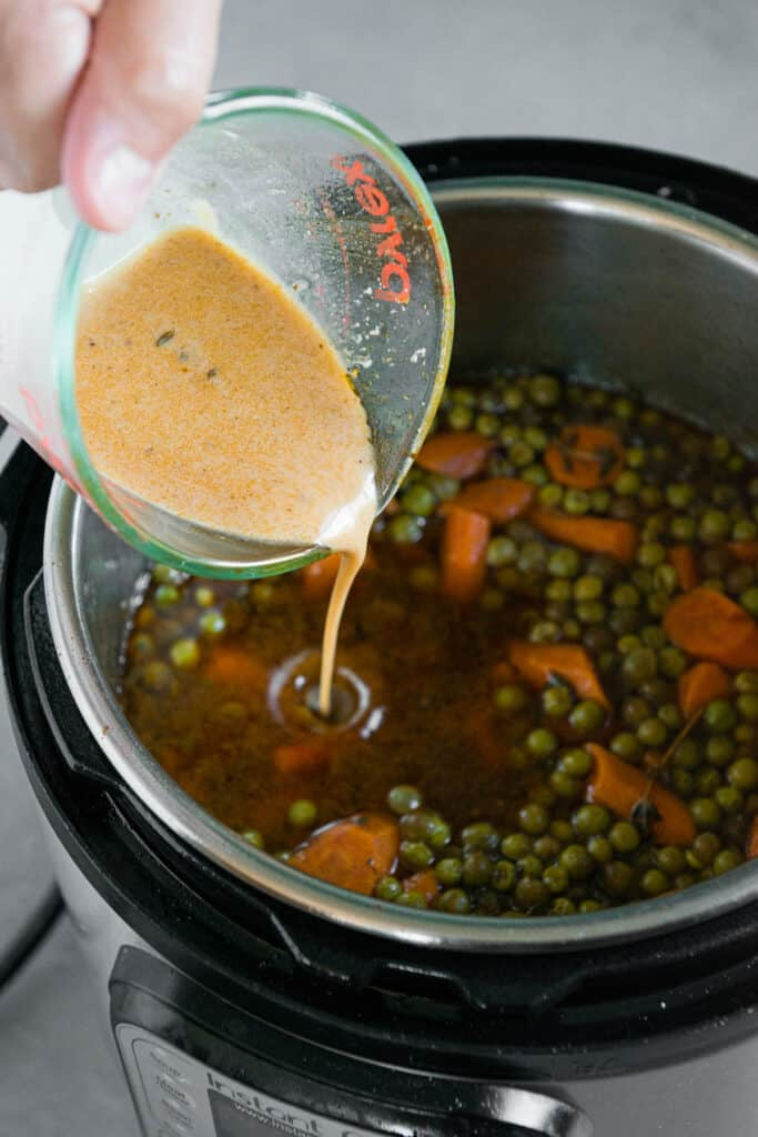pouring cornstarch slurry into beef stew
