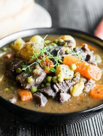 bowl of beef stew with potatoes, carrots and peas