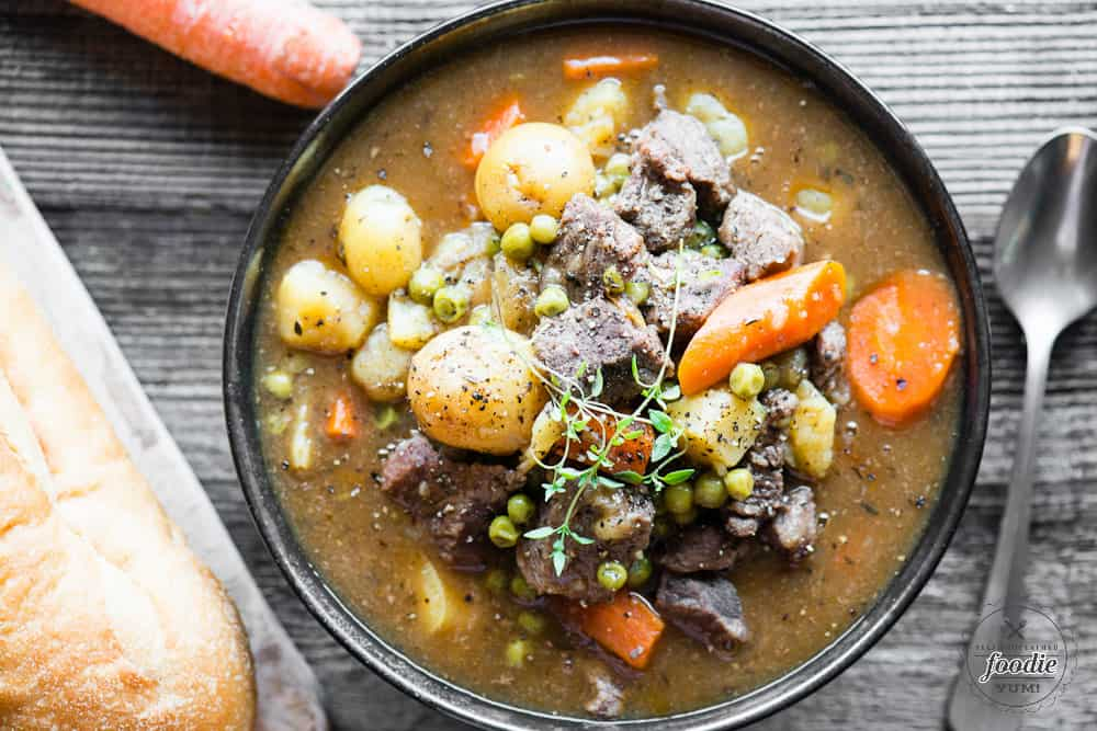 bowl of beef stew with potatoes carrots and peas