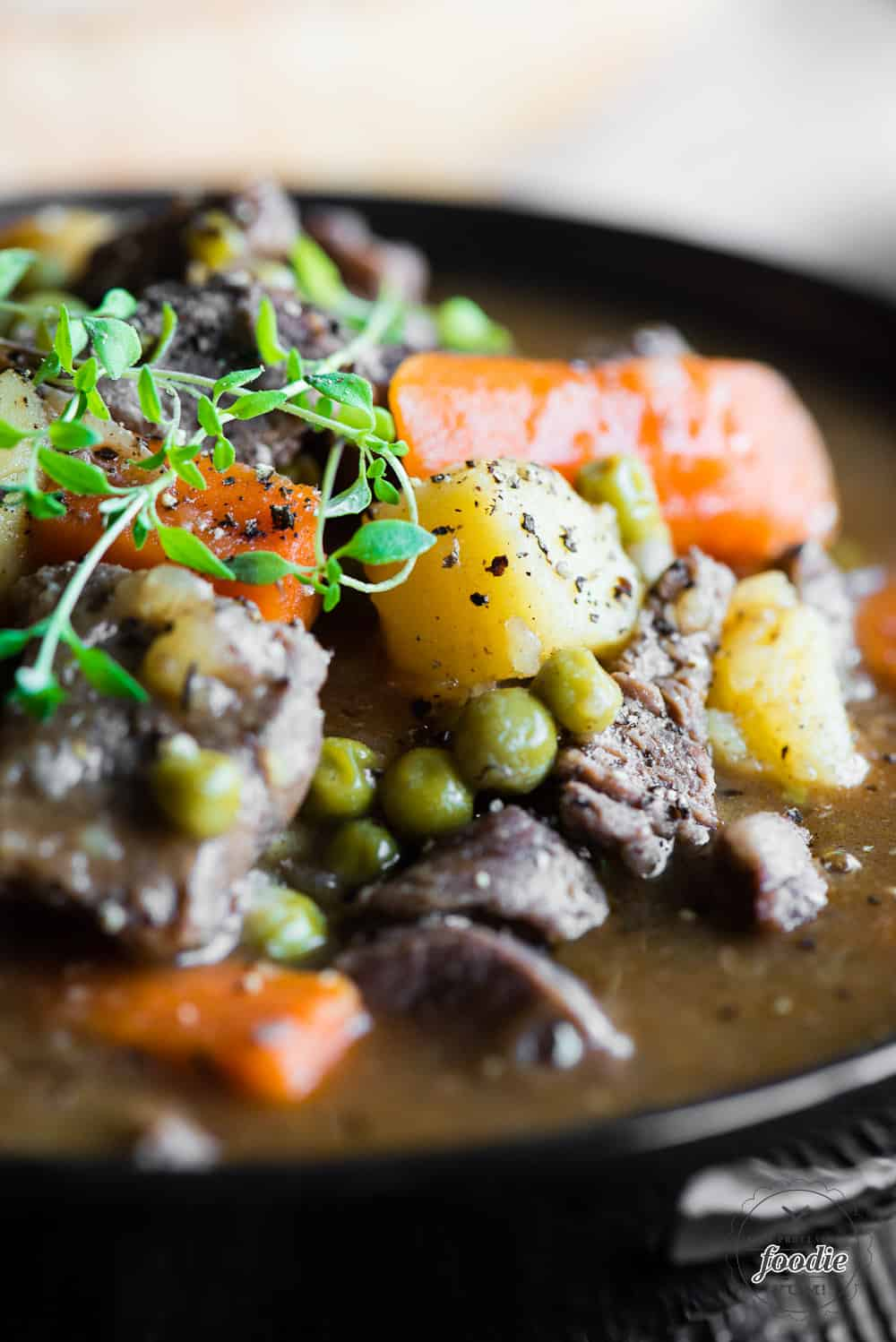close up of beef stew with potatoes, carrots and peas