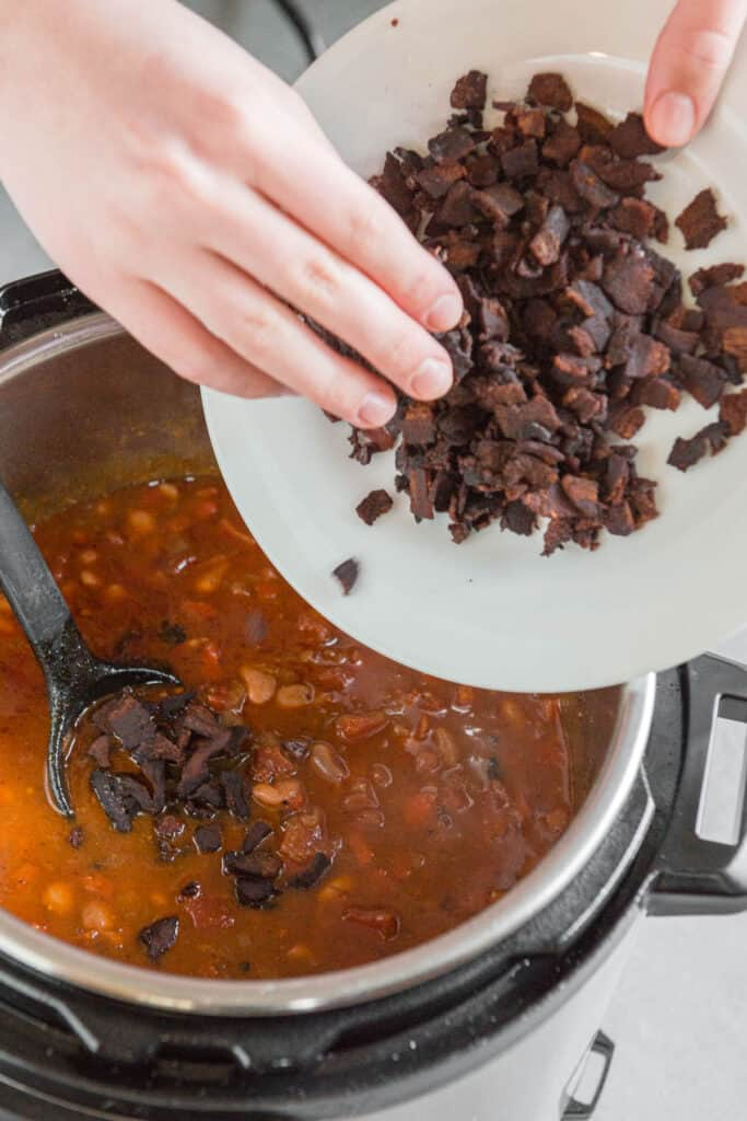 adding crisp cooked bacon to Mexican pinto beans