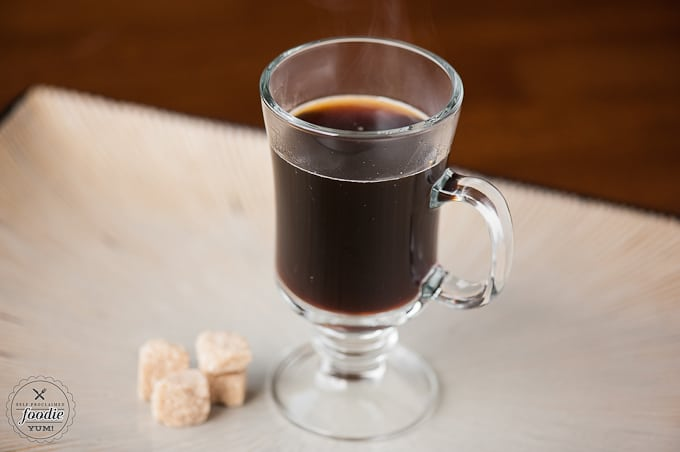 Hot black coffee in glass with sugar cubes on the side