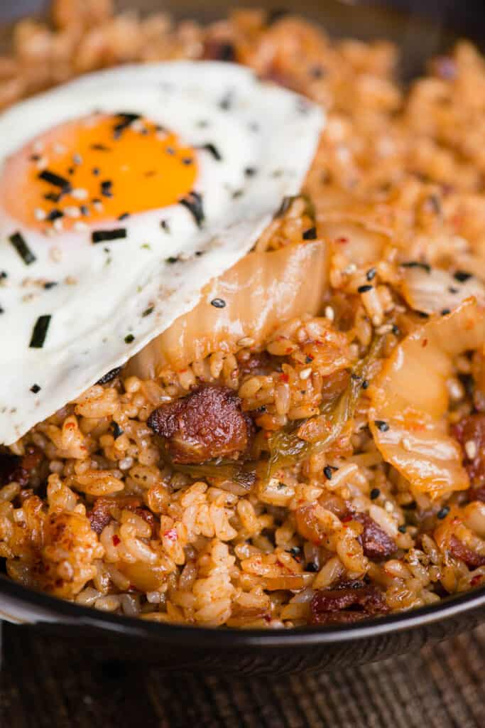 close up of kimchi fried rice with bacon and fried egg
