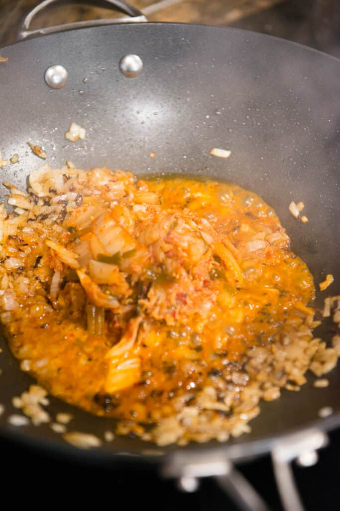 cooking kimchi and onion in wok pan