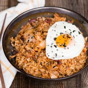 kimchi fried rice with bacon topped with fried egg in bowl