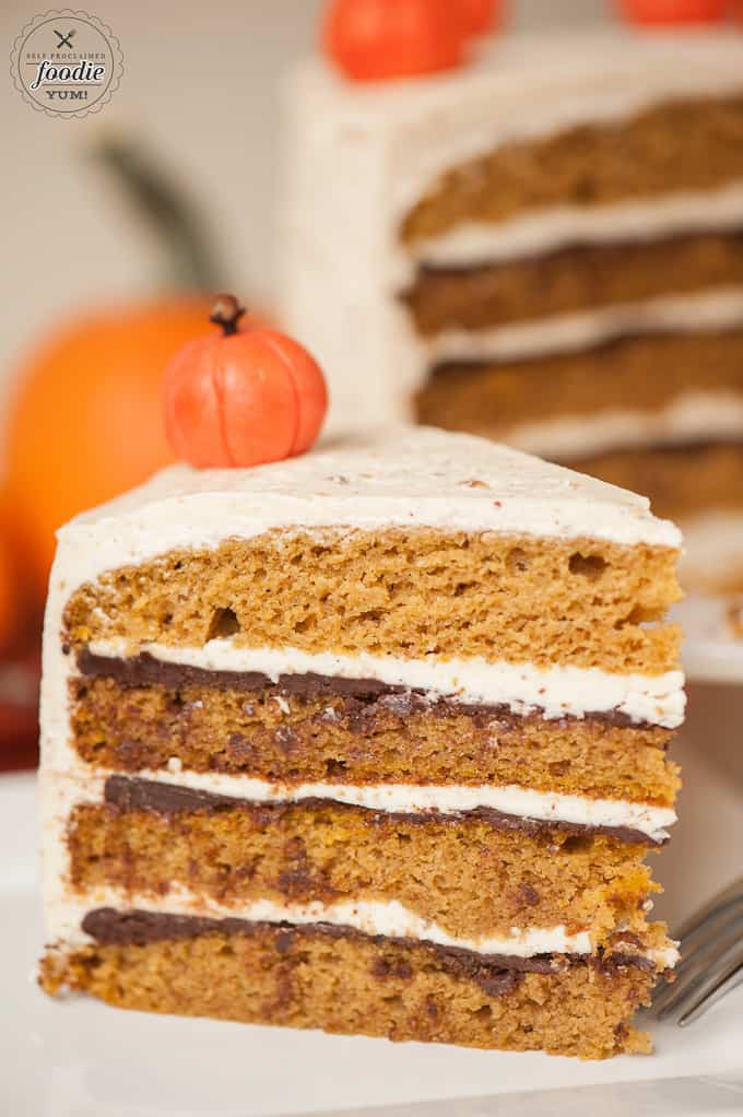sliced layered pumpkin cake showing chocolate ganache and buttercream frosting