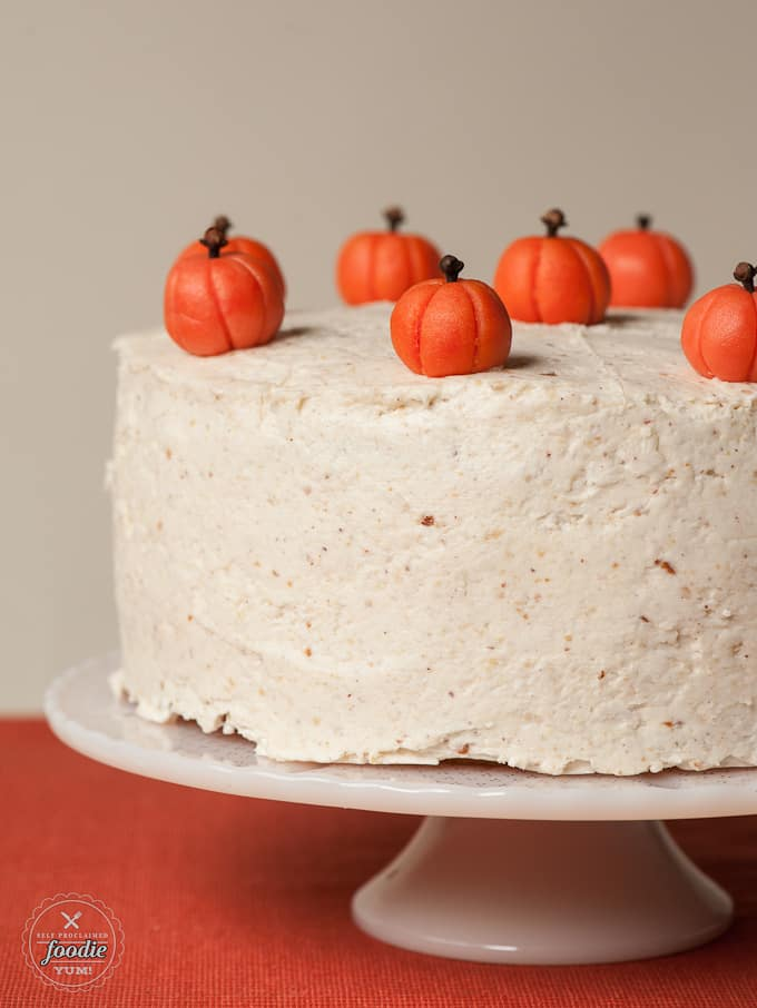 frosted layered pumpkin cake covered with marzipan pumpkins