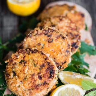 golden brown lemon basil salmon patties with lemon and lemon basil garnish