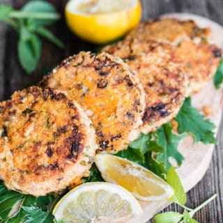Four lemon basil salmon patties on platter with lemon