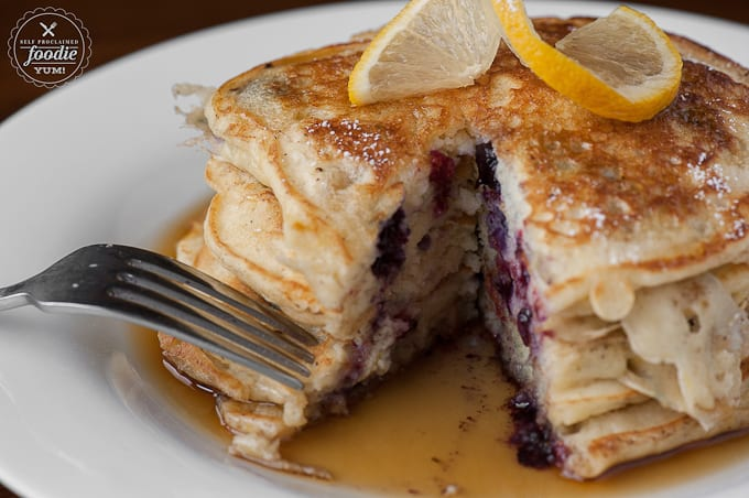 Start your morning off right with the most fluffy and flavorful Lemon Blueberry Buttermilk Pancakes with warm maple syrup for breakfast. YUM!