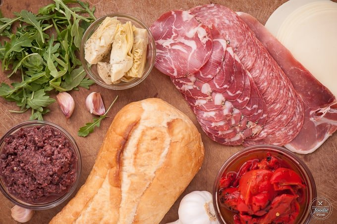 italian sandwich ingredients like meat, olive tapanade, bread