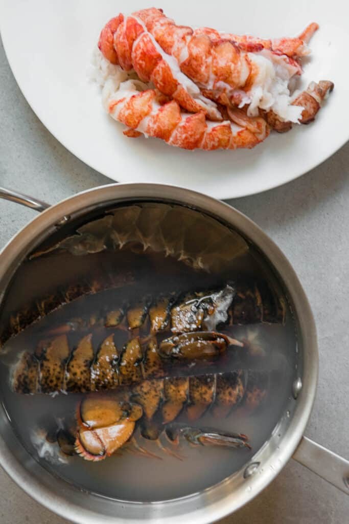 lobster tail shells in water with meat on plate