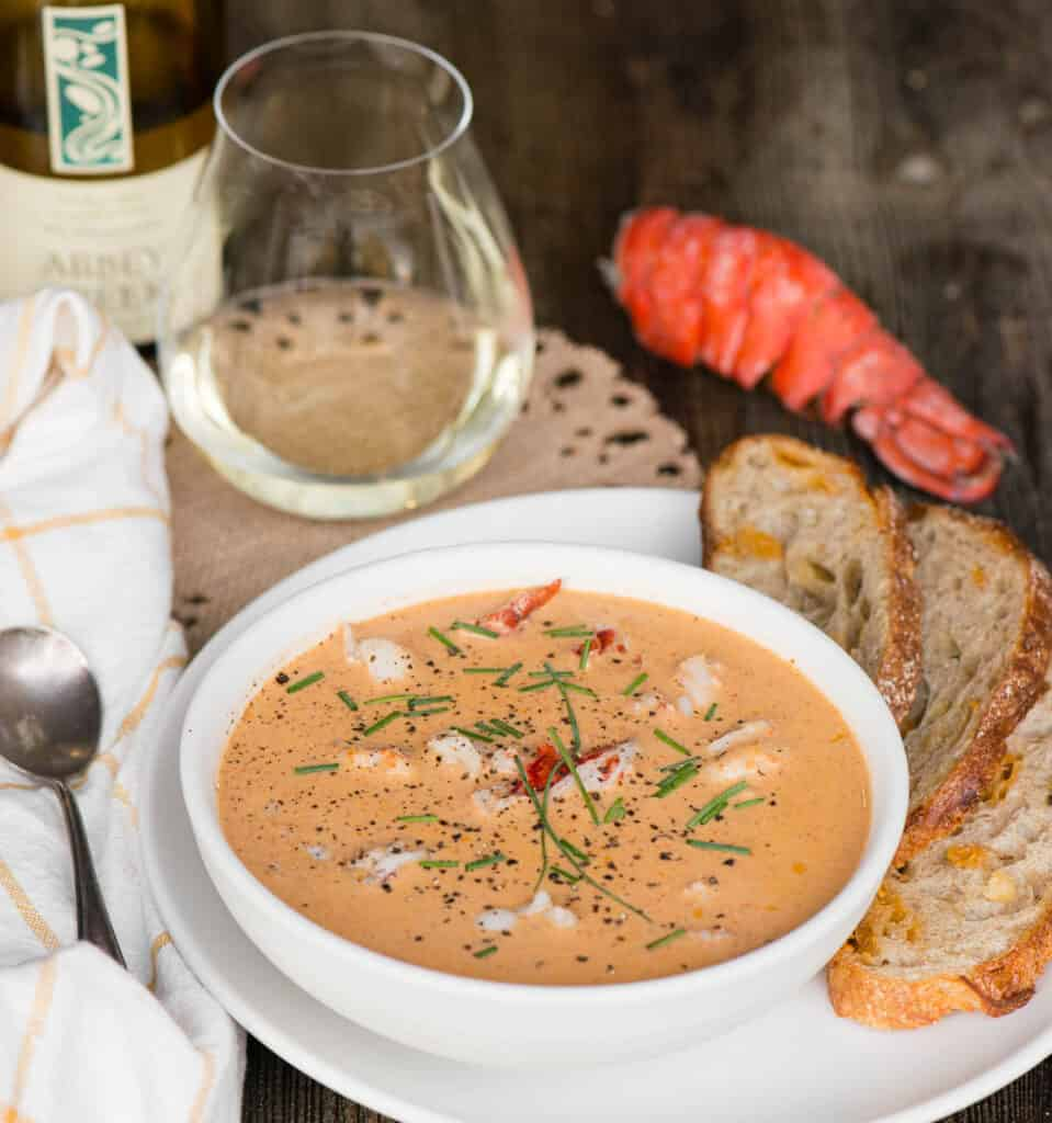 homemade lobster bisque with glass of wine and bread on side