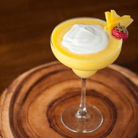 A margarita glass with a Mango Coconut daiquiri with a cream topping and garnish