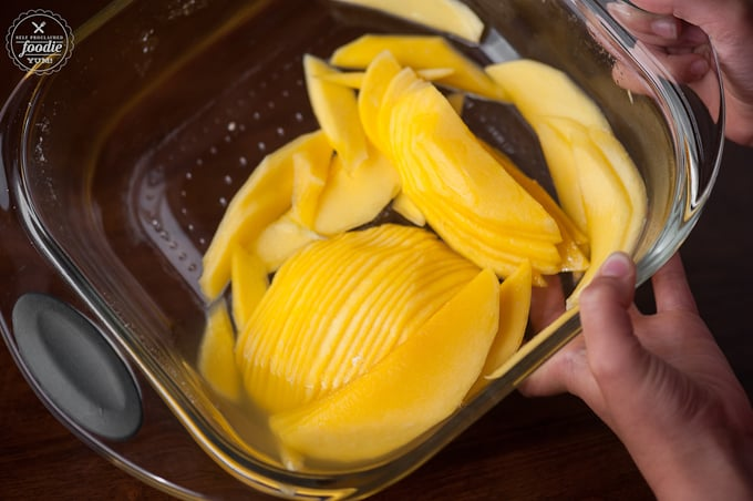 thinly sliced mango in glass pan