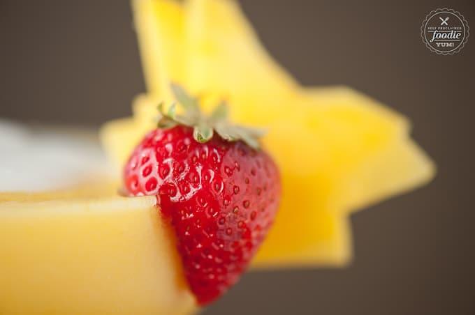 A close up of a strawberry and mango garnish