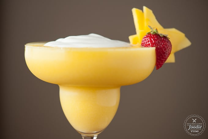 a close up of a blended coconut mango daiquiri with strawberry garnish