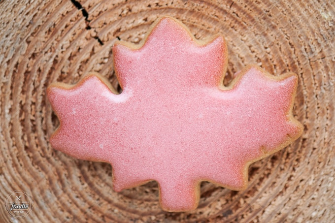 pink maple leaf sugar cookie on wood surface