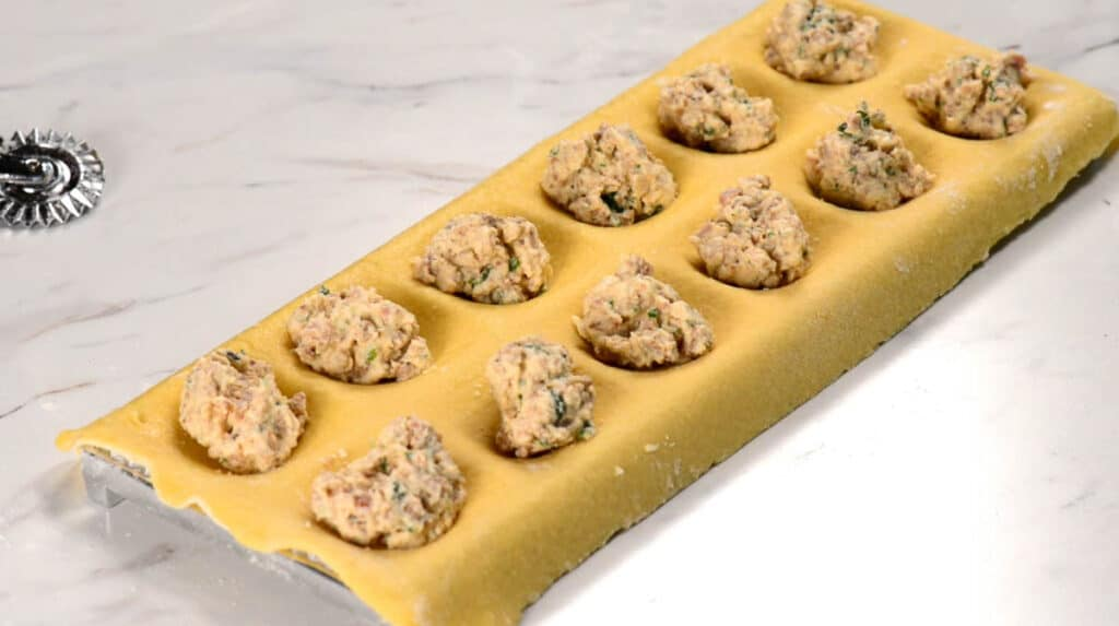 adding filling to pasta sheets for homemade ravioli