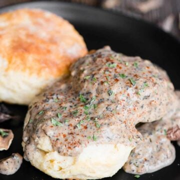black plate with two homemade buttermilk biscuits topped with vegetarian country mushroom gravy