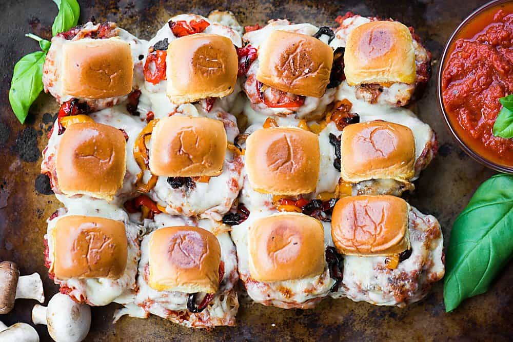 a dozen homemade mushroom ground beef sliders with sauce, peppers and cheese