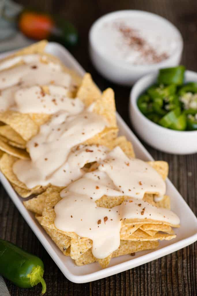 platter of nachos with homemade cheddar cheese sauce