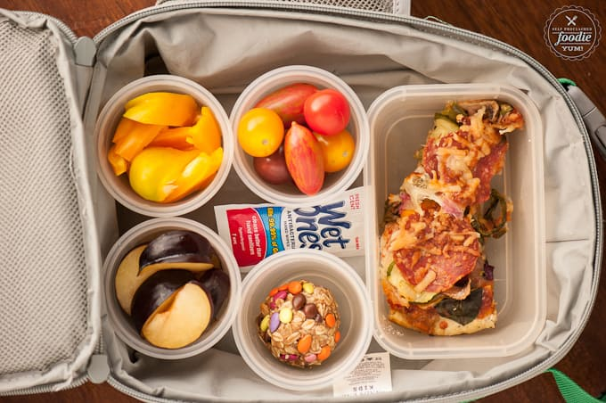 lunchbox with pizza, tomatoes, peppers, plum