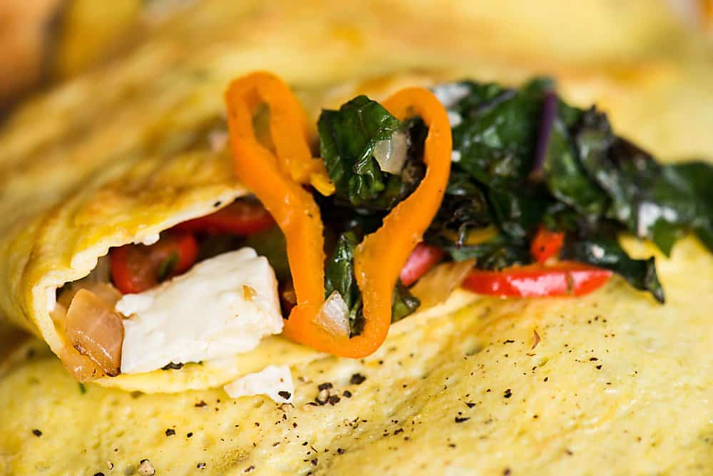 A close up of veggies inside an omelet