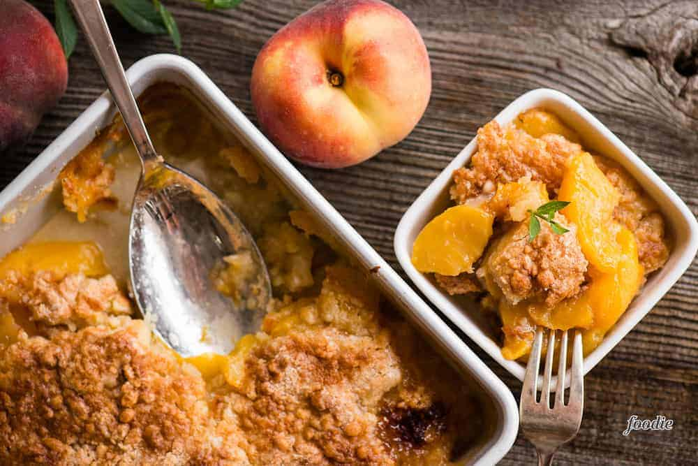 Top view ofeasy peach cobbler with crunchy in dish and pan