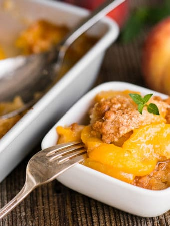 peach cobbler in dish with fork
