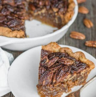 slice of pecan pie on white plate with pie behind it