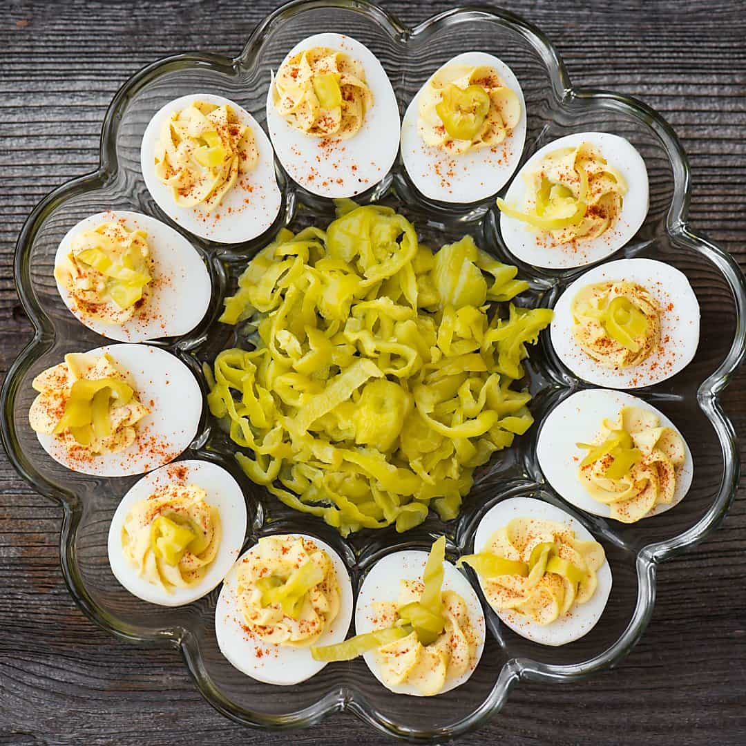 tray of deviled eggs with pepperoncinis in the middle
