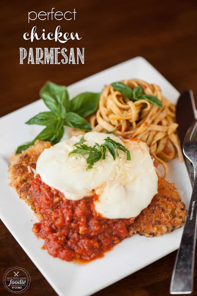 homemade chicken parmesan with pasta on plate with basil