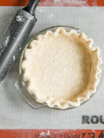 homemade butter pie crust in dish with rolling pin