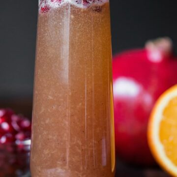 A close up of a glass of pomegranate mimosa
