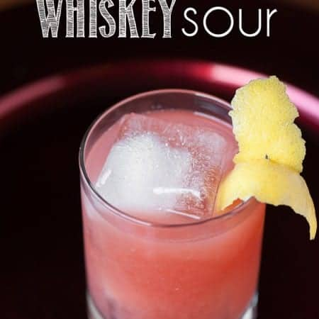 A glass of pomegranate Whiskey sour with lemon garnish