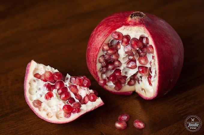 a fresh pomegranate with a piece cut out on wood table