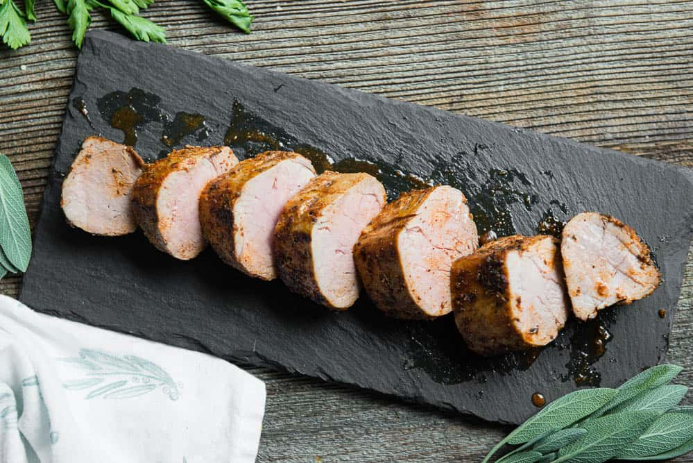 sliced pork tenderloin on black platter