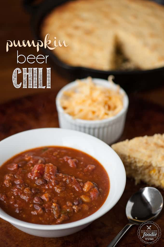 pumpkin beer chili with cheese and cornbread in the background