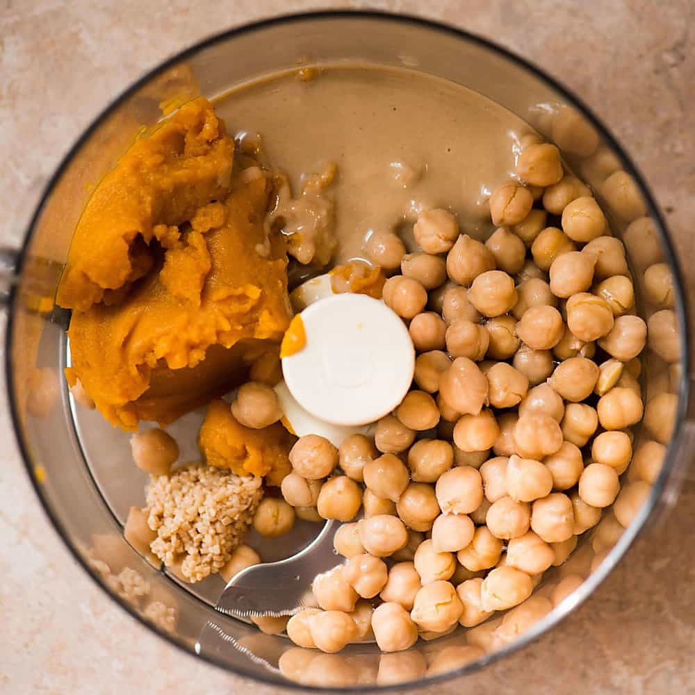 a bowl with the ingredients of pumpkin curry hummus
