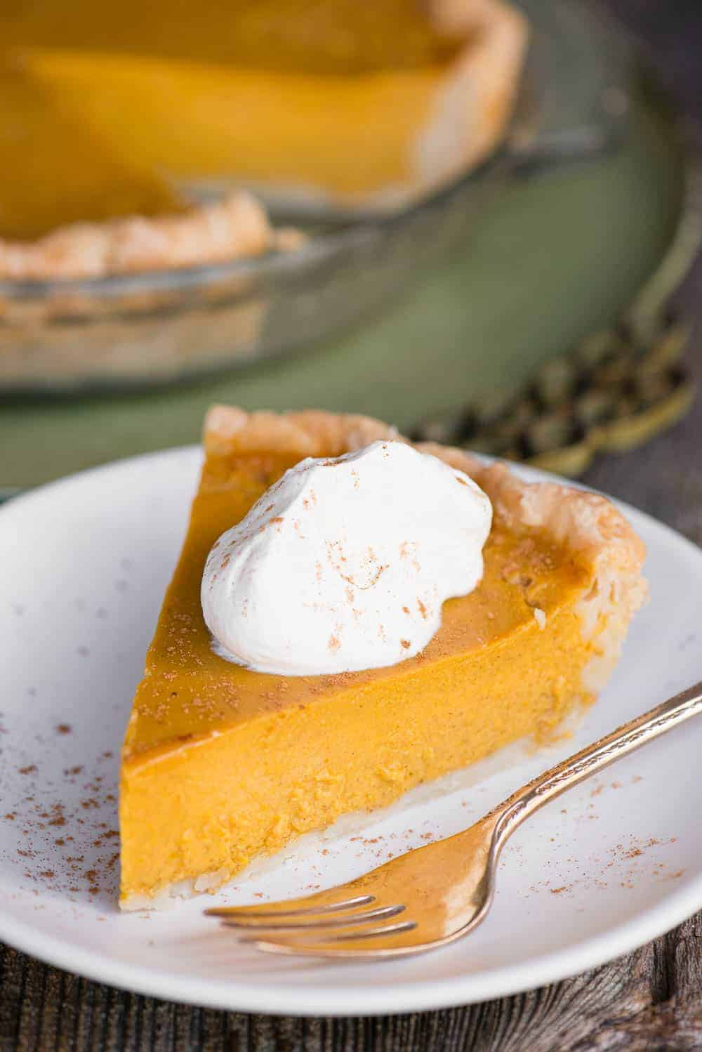 slice of Homemade classic Pumpkin Pie with whipped cream