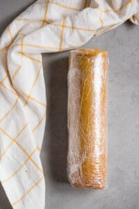 Pumpkin Roll that has been wrapped in plastic wrap