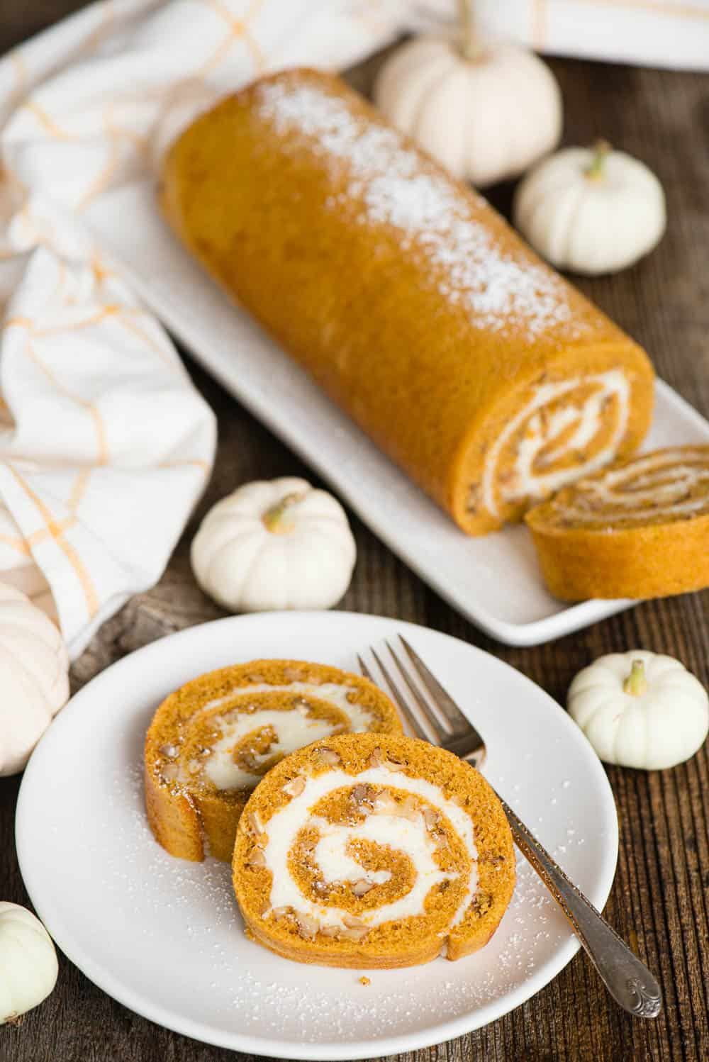 pumpkin spice roll on platter with two pieces on plate