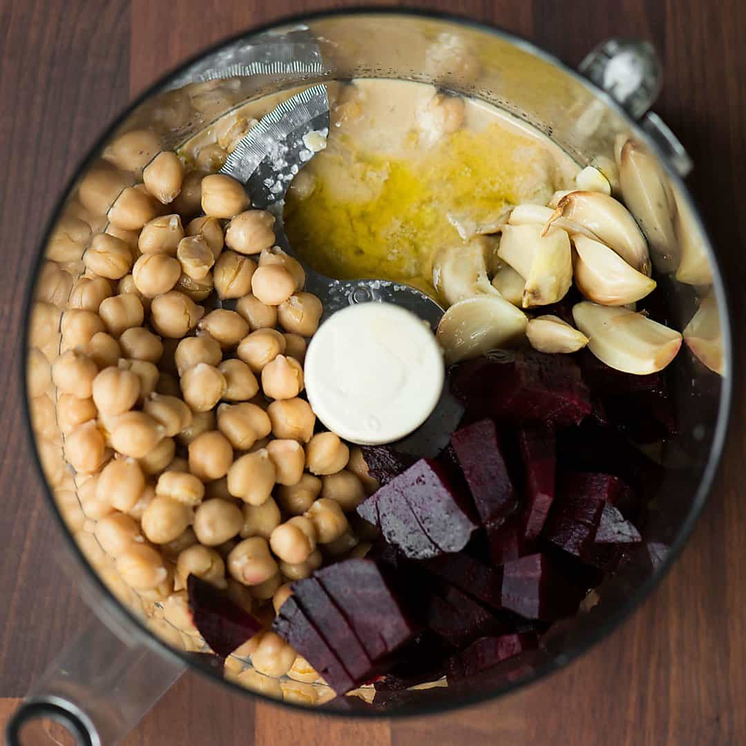ingredients for roasted garlic beet hummus preblended in a blender