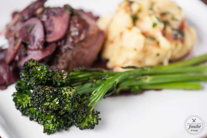 broccolini with meat and mashed potatoes on a plate