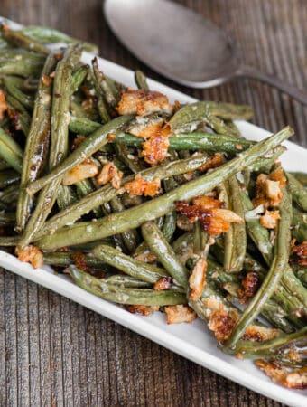 Garlic Roasted Green Beans on white rectangle platter