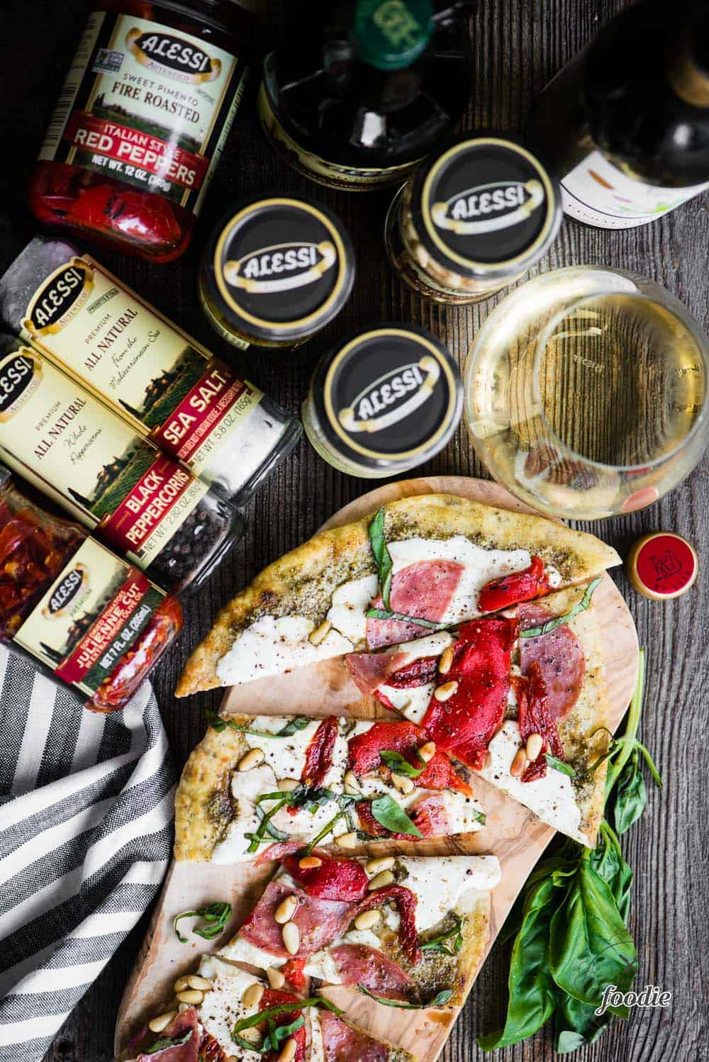 cut flatbread pizza with ingredients for toppings and a glass of wine