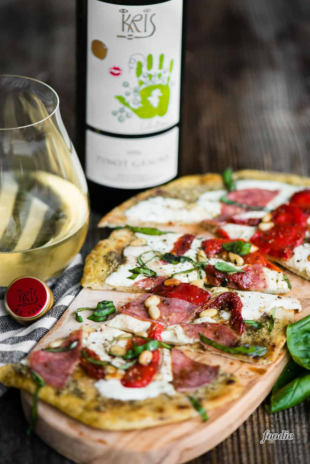 rustic homemade flatbread pizza with a glass of pinot grigio